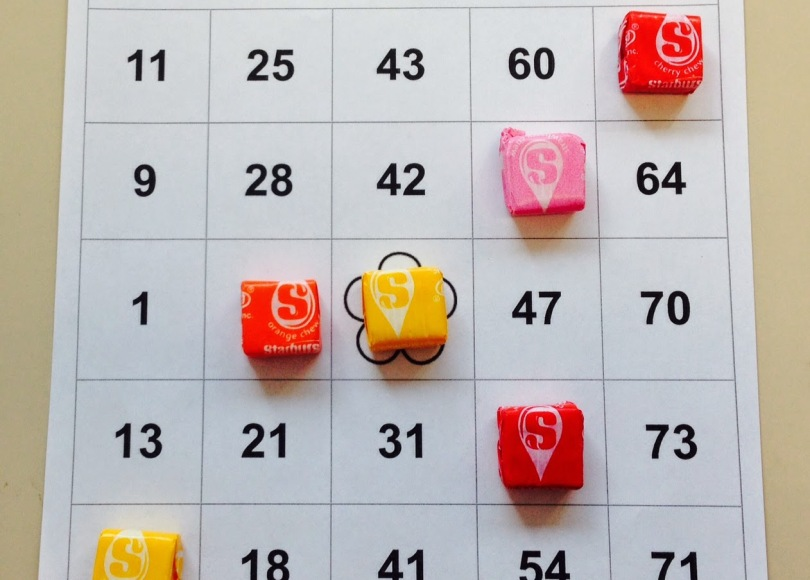 Wrapped Starburst candy are used as markers on a bingo card.